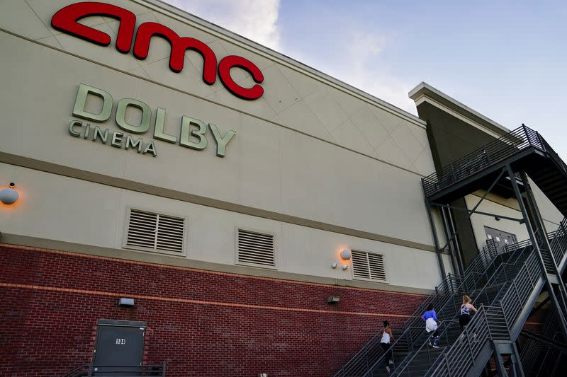 Three women use the emergency exit stairs of an AMC movie theater as a makeshift gym in Smyrna