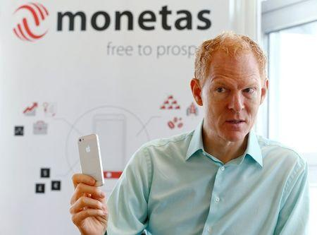 Johann Gevers, founder and CEO of Monetas, holds a mobile phone during an interview with Reuters in Zug, Switzerland, August 30, 2016. REUTERS/Arnd Wiegmann