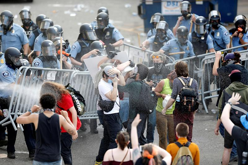 Police spray mace at protesters to break up a gathering near the Minneapolis Police third precinct on May 27 after a white police officer was caught on a bystander's video pressing his knee into the neck of a Black man named George Floyd, who later died at a nearby hospital. (Photo: Eric Miller / Reuters)