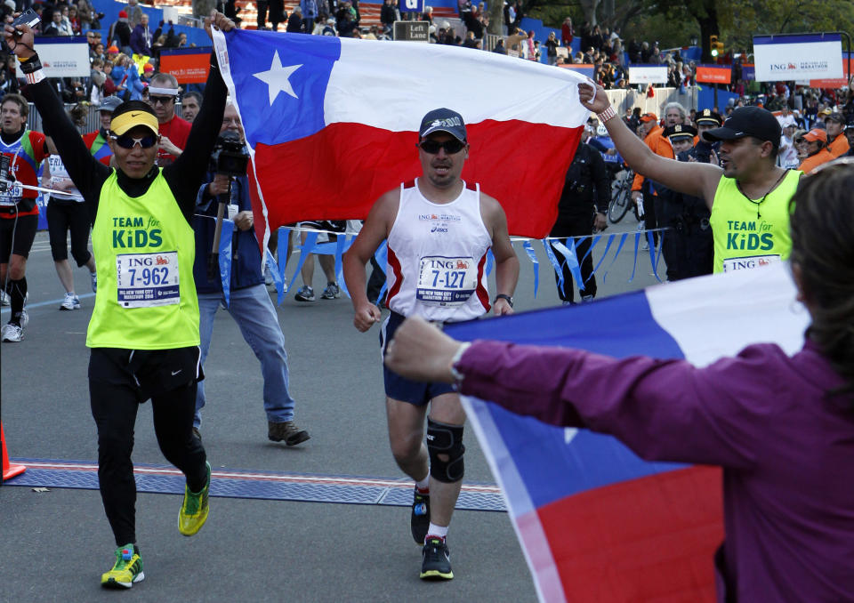 Chilean miner Edison Pena (C) crosses the finish line of the New York City Marathon, November 7, 2010. At far right is Pena' wife Angelica Alvarez holding a Chilean flag.  REUTERS/Mike Segar   (UNITED STATES - Tags: SPORT ATHLETICS)