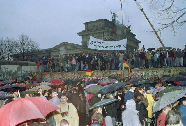 FILE - This Dec. 22, 1989 file photo shows thousands of Berliners crowding at the Brandenburg Gate and stand on top of the Berlin Wall after two new crossings were made, reuniting the divided city after 28 years. In 2014, Berlin will mark 25 years since the wall was breached. Events and exhibits commemorating the anniversary will include an installation of illuminated balloons on a 7.5-mile path where Berlin was once divided by the wall into East and West. (AP Photo/Michel Lipchitz, File)