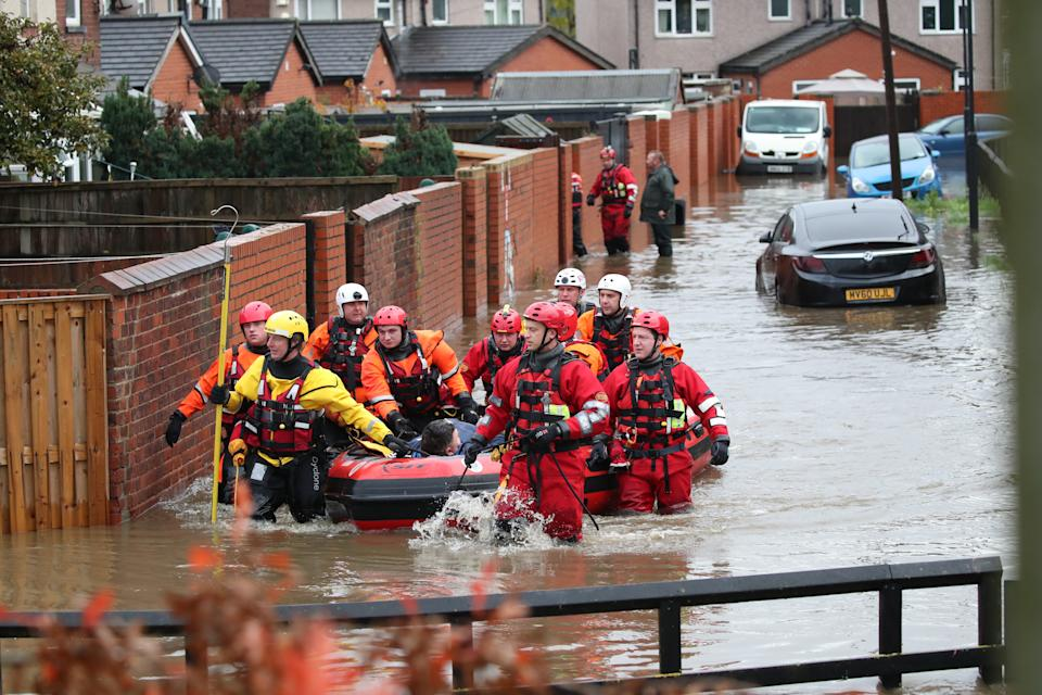 Fire and Rescue service members pull an inflatable boat that has been used to rescue residents trapped by floodwater in in Doncaster, Yorkshire, as parts of England endured a month's worth of rain in 24 hours, with scores of people rescued or forced to evacuate their homes, others stranded overnight in a shopping centre, and travel plans thrown into chaos.