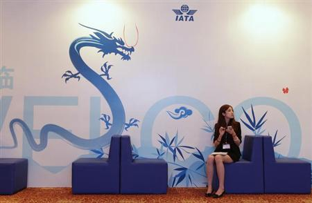 A staff member from the 68th International Air Transport Association (IATA) annual general meeting sits in front of a poster, in Beijing June 10, 2012. REUTERS/Jason Lee/Files