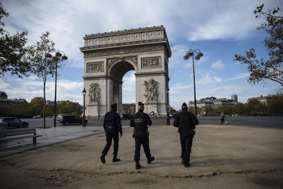 Police officers patrol by the Arc de Triomphe near the Champs Elysees avenue in Paris, Saturday, Oct. 31, 2020. France re-imposed a monthlong nationwide lockdown Friday aimed at slowing the spread of the virus, closing all non-essential business and forbidding people from going beyond one kilometer from their homes except to go to school or a few other essential reasons. (AP Photo/Lewis Joly)