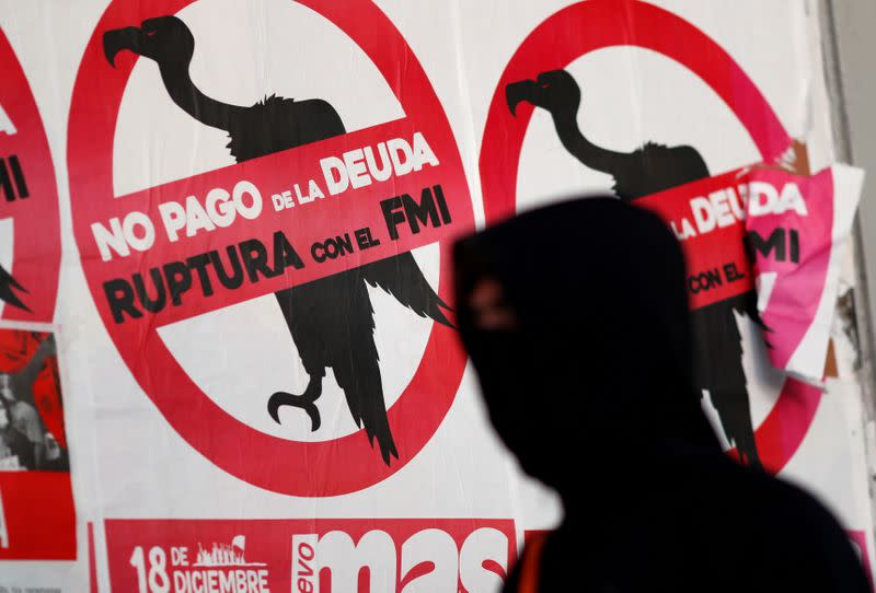 "FILE PHOTO: A pedestrian wearing a face mask walks past posters on the street that read ""No to the payment of the debt. Break with the IMF"", in Buenos Aires"