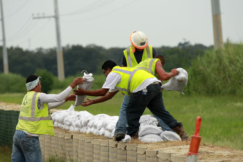 Workers stack sandbags on top of retaining wall baskets in preparation for Tropical Storm Isaac, which is expected to make landfall on the Louisiana coast as a hurricane, in Port Sulphur, La., Monday, Aug. 27, 2012. (AP Photo/Gerald Herbert)
