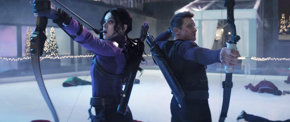 Kate and Clint back-to-back with their bow and arrows at the ready