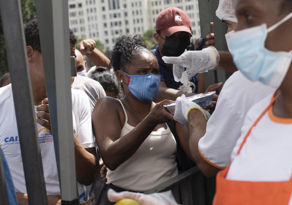 A woman receives a plate of food donated by the Leao Xlll Foundation amid the COVID-19 pandemic in Rio de Janeiro, Brazil, Wednesday, April 7, 2021. (AP Photo/Silvia Izquierdo)