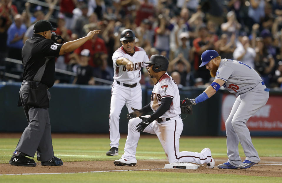 Arizona Diamondbacks' Eduardo Escobar reacts in front of Los Angeles Dodgers third baseman Justin Turner (10) after hitting a triple during the 11th inning during a baseball game Wednesday, June 5, 2019, in Phoenix. The Diamondbacks defeated the Dodgers 3-2. (AP Photo/Rick Scuteri)