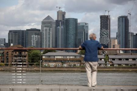 A man looks out onto the Canary Wharf financial district in London