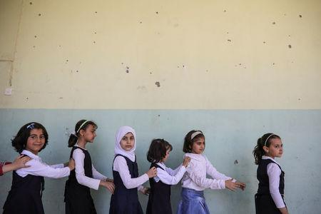 Pupils walk out from their classroom at an elementary school in eastern Mosul, Iraq, April 17, 2017. REUTERS/Marko Djurica