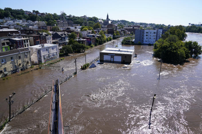 The Schuylkill River exceeds its bank in the Manayunk section of Philadelphia, Thursday, Sept. 2, 2021 in the aftermath of downpours and high winds from the remnants of Hurricane Ida that hit the area. (AP Photo/Matt Rourke)