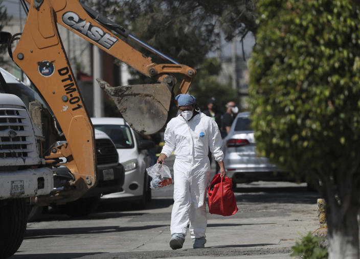 A forensic investigator carries equipment outside the house where police found bones under the floor in the Atizapan municipality of the State of Mexico, Thursday, May 20, 2021. Police have turned up bones and other evidence under the floor of the house where a man was arrested for allegedly stabbing a woman to death and hacking up her body. (AP Photo/Fernando Llano)