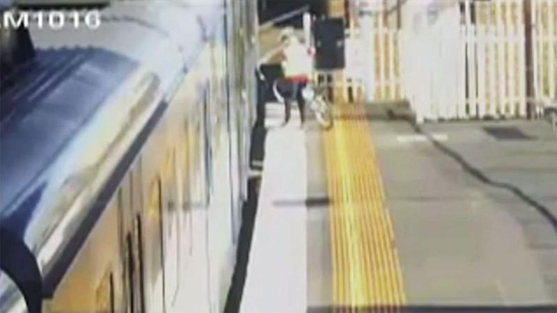 Zari was the last member of his family to board the train and can be seen attempting to push his bike on to the carriage. Photo: 7 News