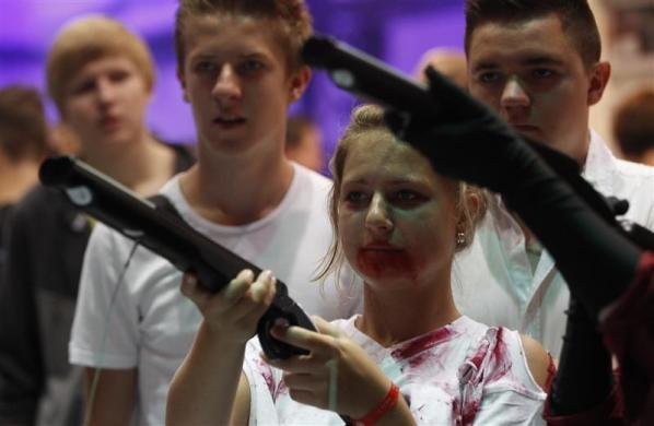 """A visitor dressed like a zombie, plays """"Dangerous Animals"""" during the Gamescom 2012 fair in Cologne August 16, 2012."""