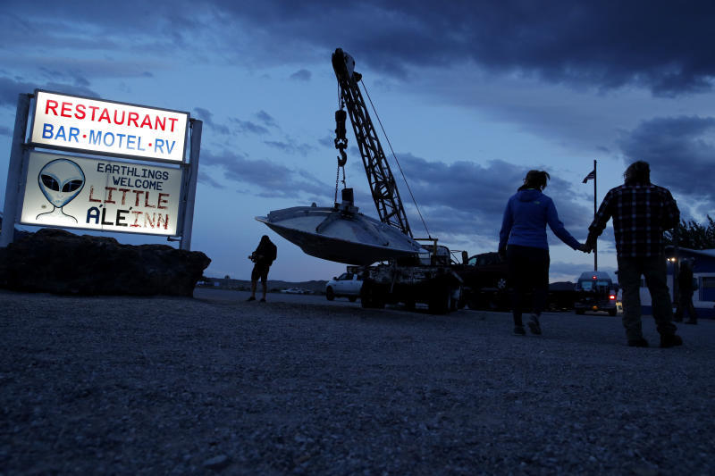 """People walk near the Little A'Le'Inn during an event inspired by the """"Storm Area 51"""" internet hoax, Thursday, Sept. 19, 2019, in Rachel, Nev. Hundreds have arrived in the desert after a Facebook post inviting people to """"see them aliens"""" got widespread attention and gave rise to festivals this week. (AP Photo/John Locher)"""