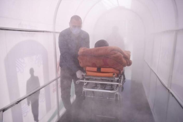 A health worker walks a patient through a disinfection chamber set up in front of a hospital in Mitrovica, Kosovo (AFP Photo/Armend NIMANI)
