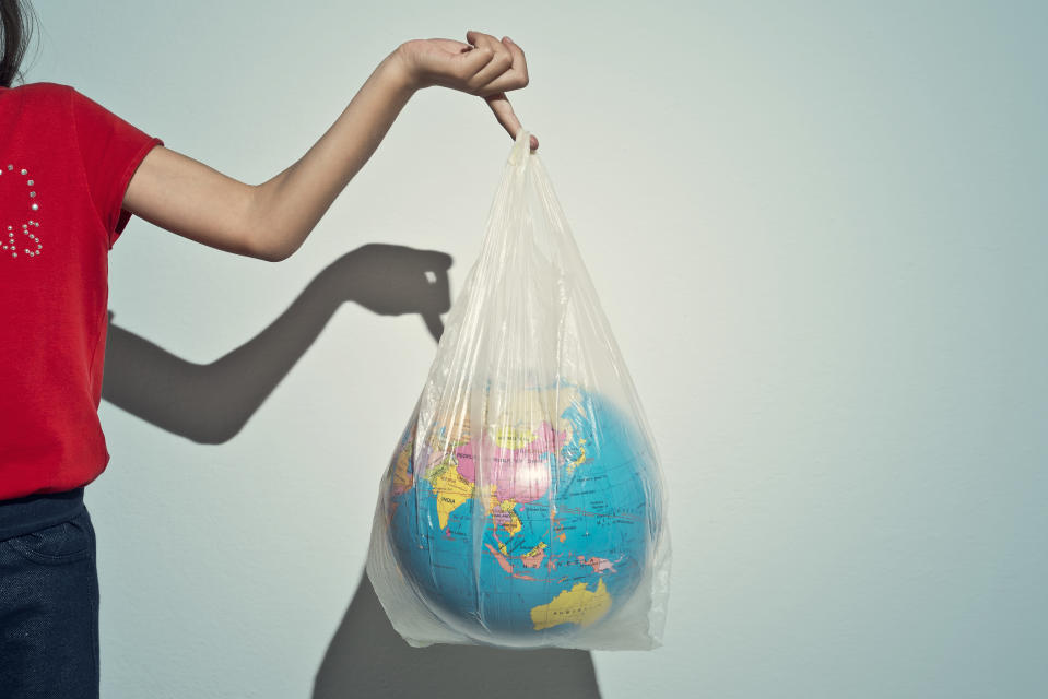 Little girl holding a plastic bag with a globe inside