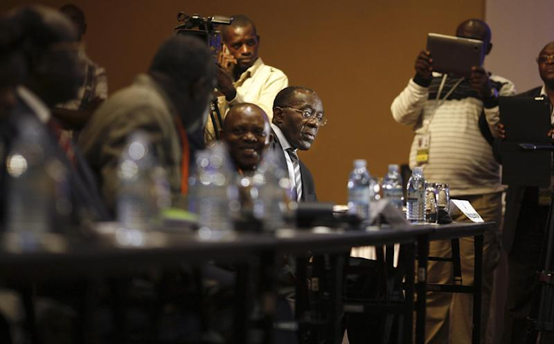 In this photo taken Sunday, Dec. 9, 2012, Congolese Foreign Minister Raymond Tshibanda looks across after listening to a speech by the leader of the delegation of Congolese M23 rebels, at peace talks between the two parties in Kampala, Uganda. Representatives of rebels attending peace talks with the Congolese government dodged a crucial meeting Monday at which the government delegation was to respond to earlier criticism, a development that could jeopardize negotiations to end the crisis in eastern Congo. (AP Photo/Rebecca Vassie)