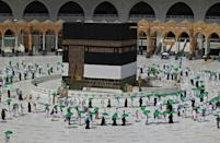 Pilgrims holding umbrellas against the sun arrive at the Kaaba at the start of the hajj on July 17