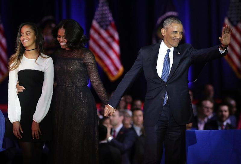 """US President Barack Obama paid tribute to First Lady Michelle Obama (C) and addressed his daughters, praising the """"two amazing young women"""" they had become"""
