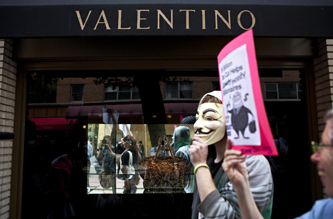 "Protestors affiliated with the ""Occupy Wall Street"" protests march past a Valentino store on East 65th Street in New York, on Tuesday, Oct. 11, 2011. The crowd marched through out the Upper East Side neighborhood, protesting outside the homes of various billionaires and bank owners. (AP Photo/Andrew Burton)"