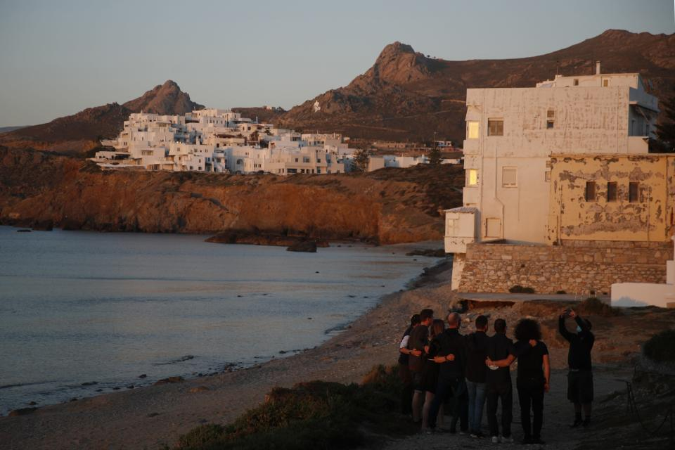 A company of tourists pose for a photograph as the sun sets in Chora, on the Aegean island of Naxos, Greece, Thursday, May 13, 2021. With debts piling up, southern European countries are racing to reopen their tourism services despite delays in rolling out a planned EU-wide travel pass. Greece Friday became the latest country to open up its vacation season as it dismantles lockdown restrictions and focuses its vaccination program on the islands. (AP Photo/Thanassis Stavrakis)