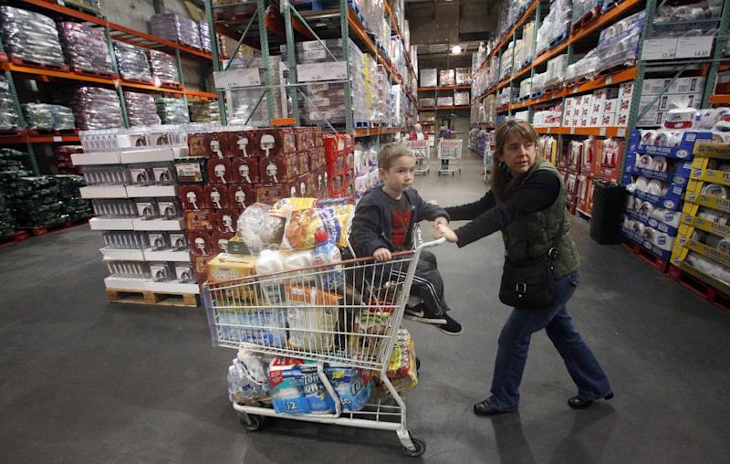 FILE - In this Dec. 7, 2011 file photo, Tina VanPelt and her son Soloman, 4, shop at a Costco wholesale store, in, Portland, Ore. Wholesale businesses increased their stockpiles in January although sales fell for the first time in eight months, according to reports Friday, March 9, 2012. (AP Photo/Rick Bowmer, File)