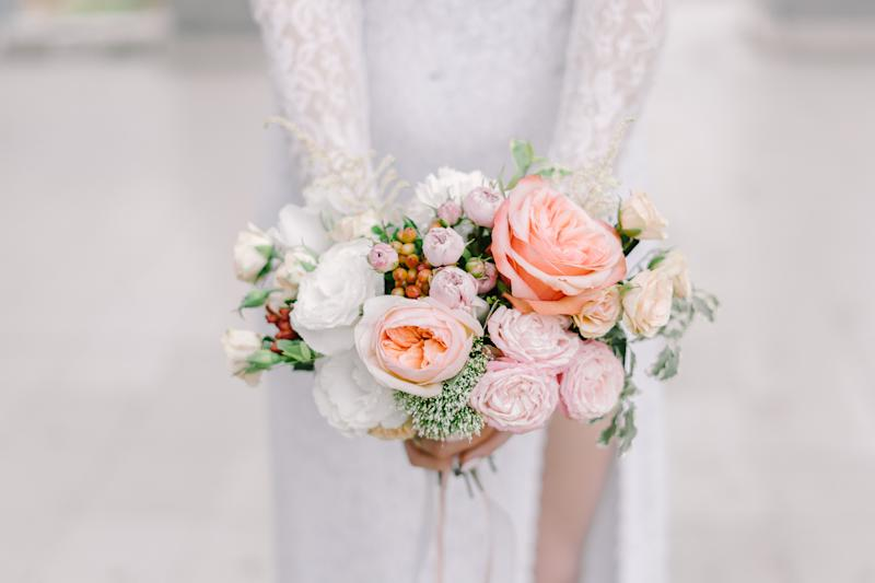 The bride holding soft wedding bouquet of roses, peonies and lisianthus, horizontal shot