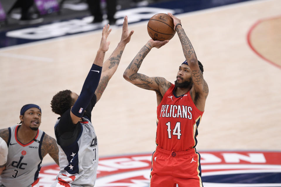 New Orleans Pelicans forward Brandon Ingram (14) shoots against Washington Wizards center Daniel Gafford, center, and guard Bradley Beal (3) during overtime in an NBA basketball game Friday, April 16, 2021, in Washington. (AP Photo/Nick Wass)