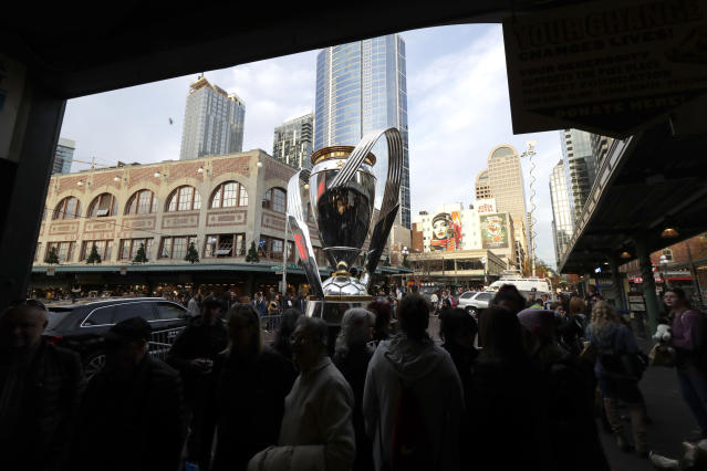 People walk past a giant replica of the MLS Cup trophy Friday, Nov. 8, 2019, on display at Pike Place Market in Seattle. Toronto FC will face the Seattle Sounders on Sunday in the MLS Cup soccer match in Seattle, the third time the two teams will have met for the MLS championship. (AP Photo/Ted S. Warren)