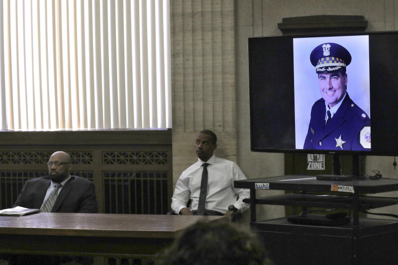 An image of Chicago Police Commander Paul Bauer during closing statements in Shomari Legghette's, left, murder trial at the Leighton Criminal Courthouse, Friday, March 13, 2020, in Chicago. Legghette is on trial for first-degree murder in the Feb. 13, 2018, killing of Chicago Police Cmdr. Paul Bauer. (Antonio Perez/Chicago Tribune via AP)