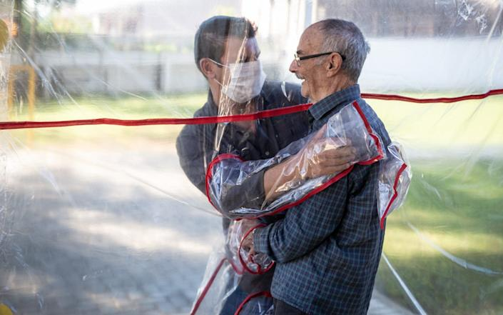 A son hugs his father using the hug tunnel after more than 70 days apart in Gravatai, Brazil - Getty