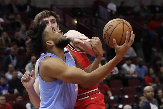 Minnesota Timberwolves center Karl-Anthony Towns, front, shoots against Chicago Bulls forward Luke Kornet during the first half of an NBA basketball game in Chicago, Wednesday, Jan. 22, 2020. (AP Photo/Nam Y. Huh)