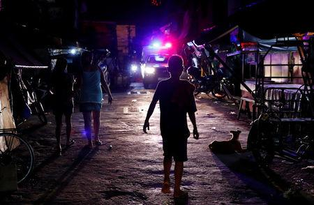 Residents walk along a street as a police vehicle patrols the streets of Tondo, Manila, Philippines July 2, 2018. REUTERS/Erik De Castro/Files