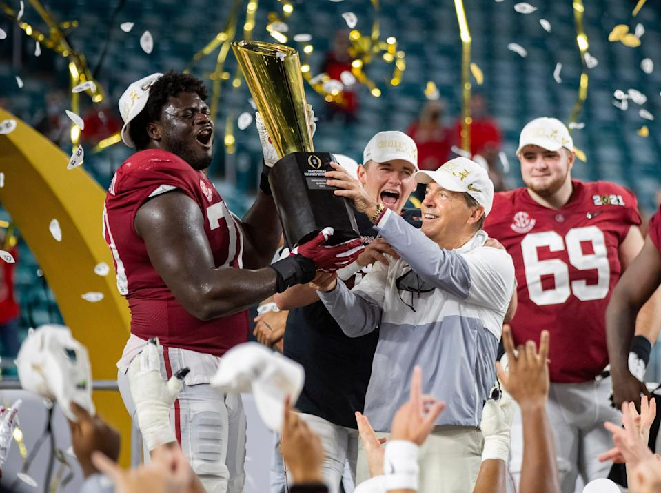 Alabama coach Nick Saban and offensive lineman Alex Leatherwood celebrated with the National Championship trophy after beating Ohio State in the 2021 CFP National Championship game.