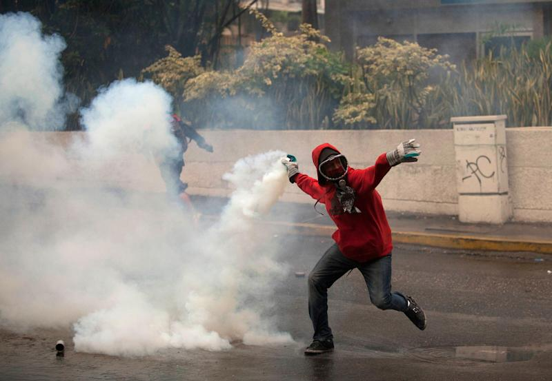 A demonstrator throws back a teargas canister fired by Bolivarian National Police after clashes broke out at an anti-government protest in Caracas, Venezuela, Thursday, May 8, 2014. Demonstrators took to the streets after a pre-dawn raid by security forces that broke up four camps maintained by student protesters and arrested more than 200 people. The tent cities were installed more than a month ago in front of the offices of the United Nations and in better-off neighborhoods in the capital to protest against President Nicolas Maduro's socialist government. (AP Photo/Alejandro Cegarra)