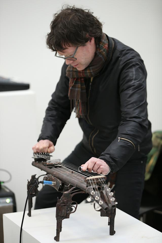 LONDON, ENGLAND - MARCH 26:  John Coxon of Spring Heel Jack plays a musical instrument made from recycled gun parts at the Lisson Gallery on March 26, 2013 in London, England.  Mexican artist Pedro Reyes received 6,700 destroyed weapons from the Mexican government from which he sculpted two groups of instruments. The first, a series titled Imagine, is an orchestra of fifty instruments, from flutes to string and percussion instruments, designed to be played live. The second, Disarm, is an installation of mechanical musical instruments, which can either be automated or played live by an individual operator using a laptop computer or midi keyboard.  (Photo by Peter Macdiarmid/Getty Images)