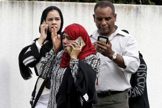 People outside the mosque speak on their phones after the attack (AP)