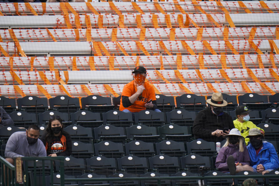 Fans are socially distanced as they watch a spring baseball game between the San Francisco Giants and the Los Angeles Angels in Scottsdale, Ariz., Sunday, Feb. 28, 2021. (AP Photo/Jae C. Hong)