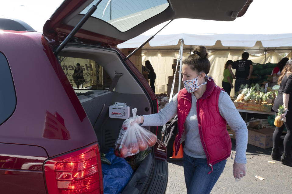 A volunteer places a bag of tomatoes into a slowly moving vehicle at a Foodshare distribution center at Rentschler Field in East Hartford, Conn., May 7, 2020, during the coronavirus pandemic. (AP Photo/Mark Lennihan)