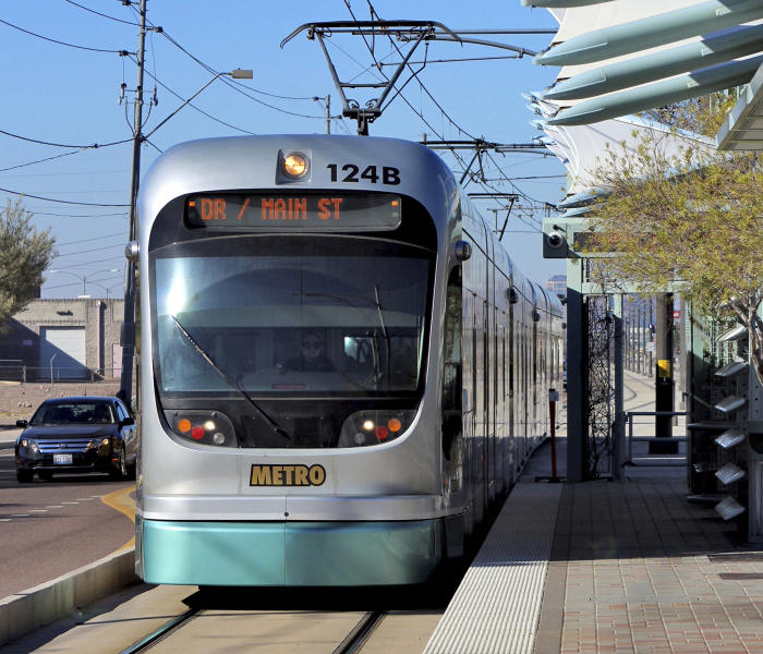 FILE - In this Jan. 16, 2016 file photo, a Metro Light Rail train stops for passengers in Phoenix. Campaigning over the future of mass rail transit in Phoenix rolled into the final stretch Monday, Aug. 26, 2019 as more voters returned early ballots weighing whether to halt all expansion of the light rail system. Early mail-in ballots have already pushed overall turnout for Tuesday's special election higher than one held four years ago at the height of the Phoenix summer, when many people leave to escape triple-digit temperatures. (AP Photo/Paul Davenport, File)
