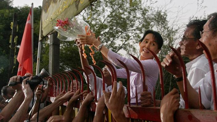 Aung San Suu Kyi greets supporters on her release from probation in 2010