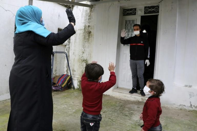 Islam Bseileh, a 29-year-old Palestinian who used to work in Israel, waves to his wife and two kids after they brought him food while he spends time in quarantine in the West Bank city of Hebron (AFP Photo/HAZEM BADER)