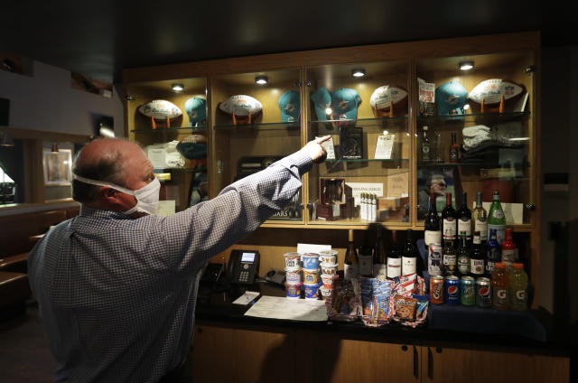 Tom Valentin, Director Of Food And Beverage for Shula's Hotel & Golf Club, shows off some memorabilia associated with former Miami Dolphins head coach Don Shula, Monday, May 4, 2020, at the hotel and golf club in Miami Lakes, Fla. Shula died Monday at his home in Indian Creek, Fla. He was 90. (AP Photo/Wilfredo Lee)