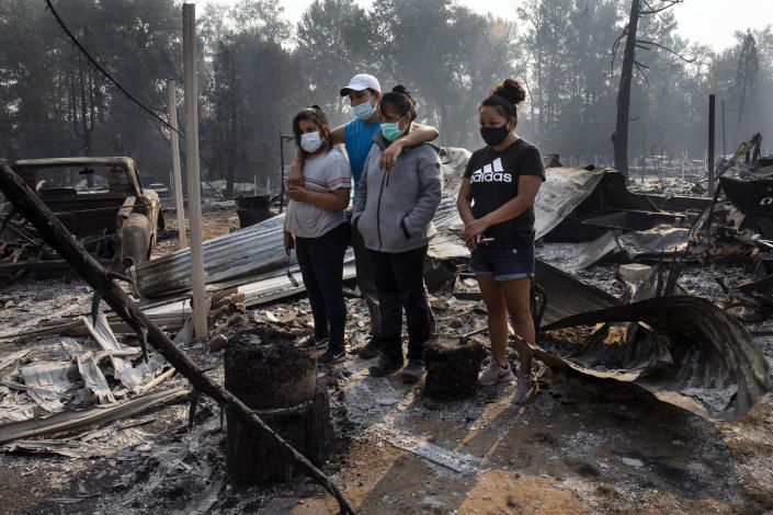 FILE - In this Sept. 10, 2020, file photo, The Reyes family looks at the destruction of their home at Coleman Creek Estates mobile home park in Phoenix, Ore. The area was destroyed when a wildfire swept through on Sept. 8. (AP Photo/Paula Bronstein, File)