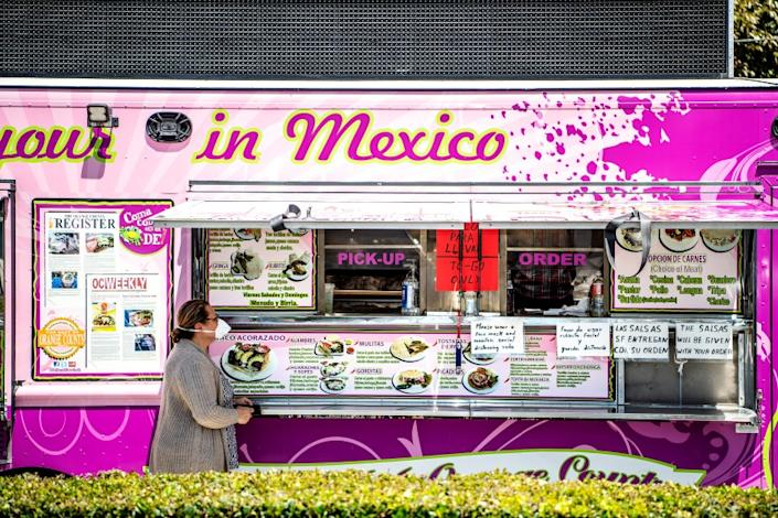 "A customer wearing a mask places an order at Alebrijes taco truck on Wednesday, April 22, 2020 in Santa Ana. span class=""copyright""(Mariah Tauger / Los Angeles Times)/span"