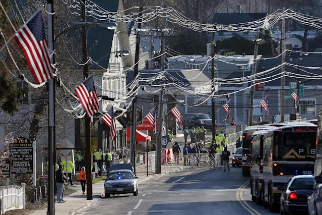 Buses carrying runners arrive at sunrise in Hopkinton, Mass., for the start of the 118th Boston Marathon Monday, April 21, 2014. (AP Photo/Michael Dwyer)