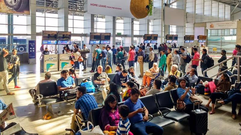People queue up to board a domestic flight while others wait for their flights at Chhatrapati Shivaji International Airport in Mumbai.
