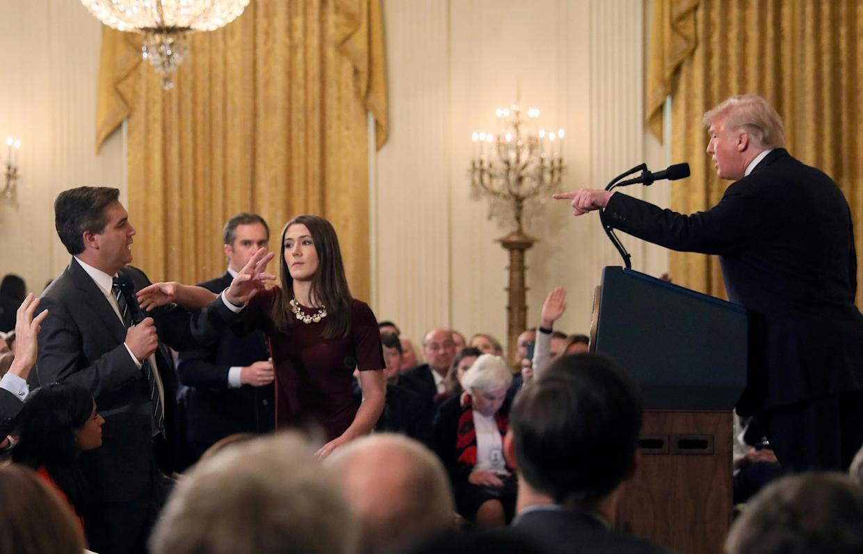 A White House staff member reaches for the microphone held by CNN's Jim Acosta as he questions President Trump during a news conference at the White House, Nov. 7, 2018. (Photo: Jonathan Ernst/Reuters)